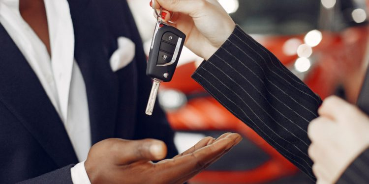 Man buying the car. Assistant helps to choose a car. Businessman in a car salon. Black male in a suit.